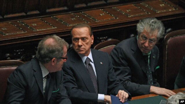 "Italian Prime Minister Silvio Berlusconi (C) holds and saves a memo reading ""308 [the result of the vote] - 8 traitors - political reversal - vote - take note: resign - Republic President - a solution"" during a budget vote at the parliament in Rome, Novem"
