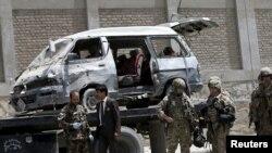Petugas keamanan Afghanistan dan asing terus mengawasi lokasi serangan bom mobil di Kabul, 17 Mei 2015.