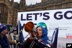A pro-European demonstrator protests in front of a Leaver campaign board opposite the Houses of Parliament in London, Jan. 15, 2019, ahead of lawmakers' vote on whether to accept British Prime Minister Theresa May's Brexit deal. Later, the plan was soundly defeated. Britain is due to leave the EU on March 29.