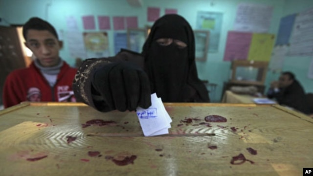 Egyptian woman casts her vote during the second round of parliamentary run-off elections, Cairo, Dec. 2011.