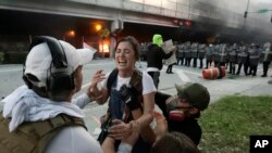 Protesters help a woman who was hit in the throat with a rubber bullet during a demonstration next to the city of Miami Police Department, May 30, 2020, downtown in Miami.