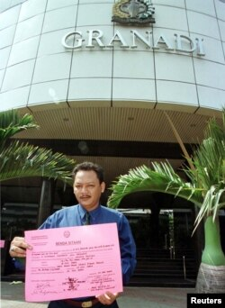 Jaksa dari Kejaksaan Agung menempelkan pengumuman penyitaan di gedung perkantoran Jakarta yang merupakan rumah bagi beberapa yayasan amal Soeharto pada 21 Juli. (Foto: Reuters)
