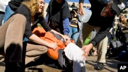 FILE - Protesters demonstrate the use of water boarding to volunteer Maboud Ebrahim Zadeh in front of the Justice Department in Washington, Nov. 5, 2007.