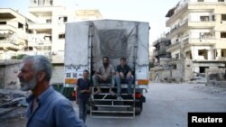 People sit on a Syrian Arab Red Crescent truck, which is part of an aid convoy in the rebel held besieged Harasta area, in the eastern Damascus suburb of Ghouta, Syria, June 19, 2017. Rebel fighters and their families are preparing to leave Harasta for other rebel-held areas.