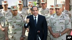 Egyptian President Abdel-Fattah el-Sissi speaks ahead of a military funeral for troops killed in an assault in the Sinai Peninsula, as he stands with army commanders, in Cairo, Egypt, Oct. 25, 2014.