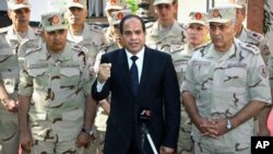 In this photo provided by Egypt's state news agency MENA, Egyptian President Abdel-Fattah el-Sissi speaks in front of the state-run TV ahead of a military funeral for troops killed in an assault in the Sinai Peninsula, as he stands with army commanders in