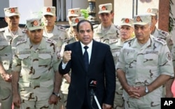 FILE - In this photo provided by Egypt's state news agency MENA, Egyptian President Abdel Fattah el-Sissi, center, speaks in front of the state-run TV ahead of a military funeral for troops killed in an assault in the Sinai Peninsula, as he stands with army commanders in Cairo, Egypt, Saturday, Oct. 25, 2014.