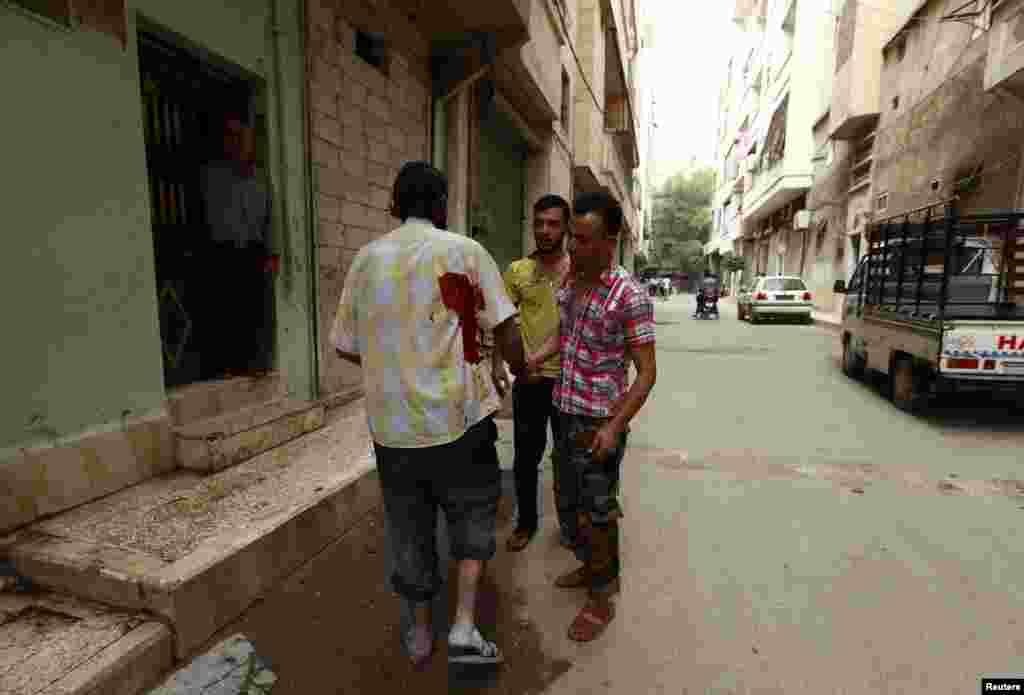 2013年9月19日,阿勒颇一个街区在遭到据称忠于叙利亚总统阿萨德的军队炮击后,一个受了伤的人在街上行走。