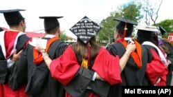 FILE - In this May 15, 2016 file photo, students embrace as they arrive for the Rutgers graduation ceremonies in Piscataway, New Jersey.