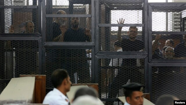 Muslim Brotherhood's General Guide Mohamed Badie (R) is pictured in a defendant's cage with other defendants in a courtroom in Cairo, June 7, 2014.