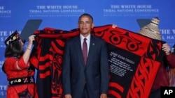 Kepala suku Mohegan Lynn Malerba (kiri), dan Brian Cladoosby, Presiden Kongres Nasional Indian Amerika menaruh selimut di bahu Presiden AS Barack Obama dalam konferensi penduduk asli di Gedung Putih (26/9). (AP/Pablo Martinez Monsivais)