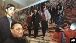 资料照:中国已故领导人邓小平的儿子邓朴方在北京军事博物馆举办的展览中观看了他父亲的一张大照片,由他的妹妹邓琳拍摄。(1998年2月18日)