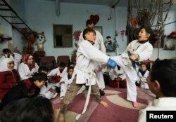 Para pemuda berlatih karate di sebuah sekolah seni bela diri di desa al-Jeineh, Suriah 11 April 2021. (REUTERS / Khalil Ashawi)