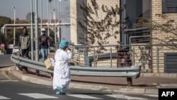 Un agent de santé sud-africain porte un équipement de protection individuelle (EPI) complet alors qu'elle se promène à l'intérieur de l'hôpital Chris Hani Baragwanath à Soweto, le 18 juillet 2020.