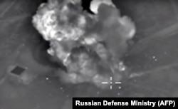 An image taken from video purports to show explosions after airstrikes carried out by Russia's air force on what it said was an Islamic State ammunition depot in the Syrian province of Idlib, Oct. 14, 2015..