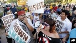 Демонстранты протестуют против закона штата Аризона о нелегальных иммигрантах. Финикс. 25 июня 2012 г.