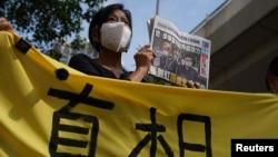 在西九龍法院的一次聽證期間,一名支持者舉著報紙在法院外聲援《蘋果日報》。(2021年6月19日)