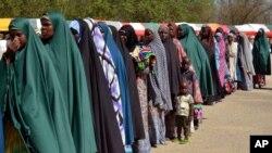 Para perempuan dan anak-anak yang ditahan atas kecurigaan keterlibatan dengan Boko Haram, berbaris saat dibebaskan oleh militer Nigeria di Maiduguri, Nigeria (6/7). (AP/Jossy Ola)