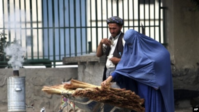 An Afghan woman clad in burqa buys a broom along a roadside in Kabul June 13, 2011.