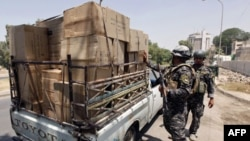 Cảnh sát xem xét một chiếc xe tại một trạm kiểm soát trên đường Abu Nawas ở Baghdad, ngày 20/6/2011