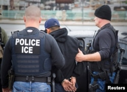 FILE - U.S. Immigration and Customs Enforcement officers detain a suspect as they conduct a targeted enforcement operation in Los Angeles, Feb. 7, 2017.