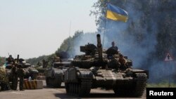 FILE - A Ukrainian army tanks moves past a checkpoint in eastern Ukraine.