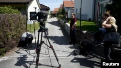 TV crews perpare for a statement in front of a house in Wuerenlingen, Switzerland, where several people were killed late Saturday, May 10, 2015.
