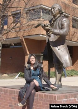 Soulin Reyes at the George Mason statue. It is considered good luck to rub the statue's foot.