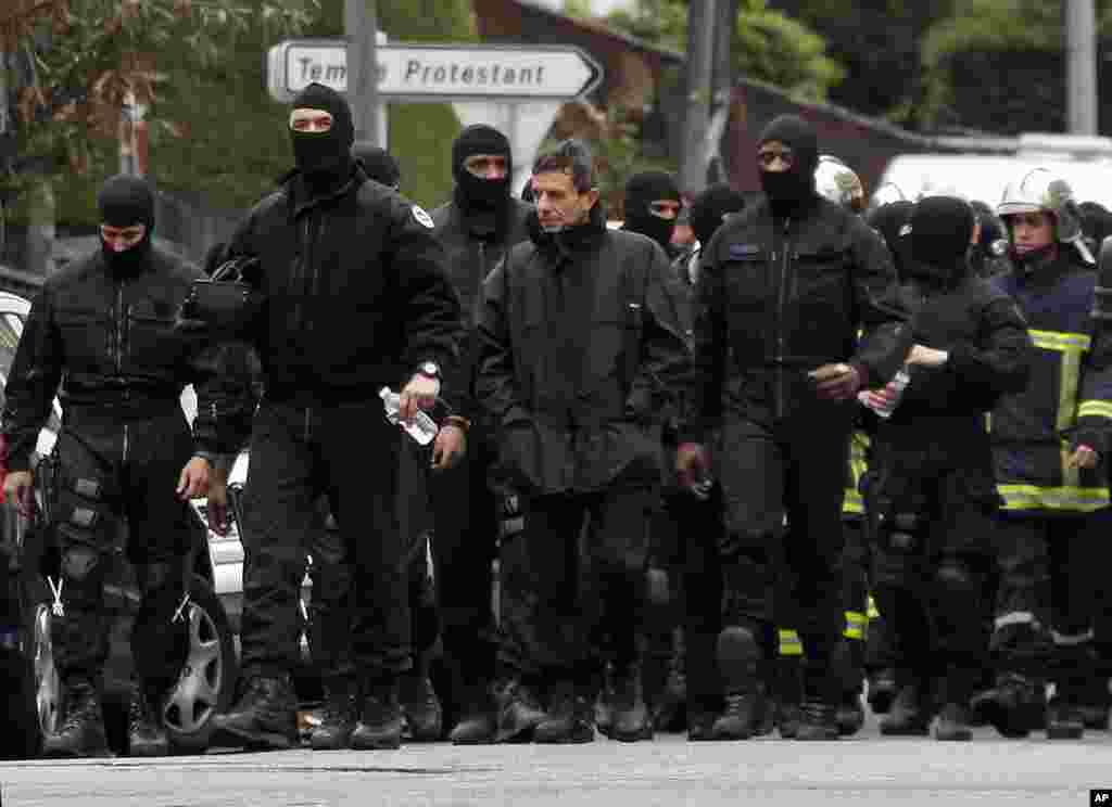 Masked French special unit policemen leave the scene after the assault to capture gunman Mohamed Merah during a raid on a building to arrest the suspect in Toulouse, March 22, 2012. (Reuters)