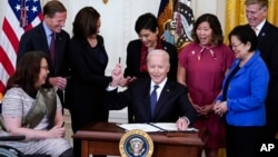 BidenPresident Joe Biden hands out a pen after signing the COVID-19 Hate Crimes Act, in the East Room of the White House, Thursday, May 20, 2021, in Washington. Clockwise from left, Sen. Tammy Duckworth, R-Ill., Sen. Richard Blumenthal, D-Conn., Vice Pres
