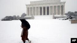 路人於風雪當中在美國首都華盛頓的林肯紀念堂前面經過