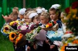 iswa kelas satu berkumpul menandai dimulainya tahun ajaran baru. Sekolah dibuka kembali setelah liburan musim panas dan lockdown karena wabah Covid-19, di Moskow, Rusia 1 September 2020. (Foto: Reuters)
