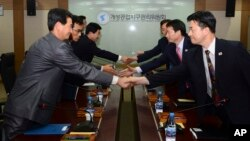 In this photo released by Unification Ministry, South Korean delegates, right, shake hands with their North Korean counterparts at Kaesong Industrial District Management Committee meeting, Kaesong, North Korea, Sept. 11, 2013.