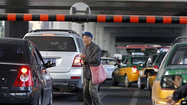 A Chinese beggar walks amongst traffic asking for a handout in Beijing, China. China's inflation rate edged lower in September, giving Chinese leaders leeway to stimulate the economy as U.S. and European growth slows, October 14, 2011.