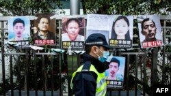 FILE - A police officer walks past placards of detained rights activists taped on the fence of the Chinese liaison office in Hong Kong, Feb. 19, 2020.