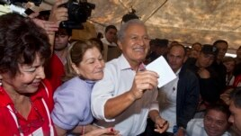 Presidential candidate Salvador Sanchez Ceren, who is also the current VP for the ruling Farabundo Marti National Liberation Front (FMLN), center, accompanied by his wife, center left, raises his ballot before casting it, El Salvador, March 9, 2014.