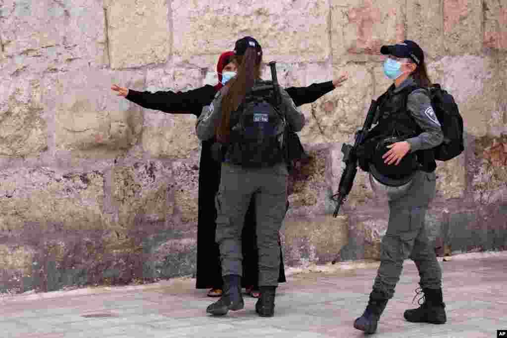 이스라엘 국경 경찰이 예루살렘에서 팔레스타인 여성의 몸을 수색하고 있다.