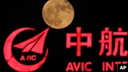 FILE - The supermoon, rises over a logo for AVIC or Aviation Industry Corp in Beijing, China, Tuesday, Nov. 15, 2016.