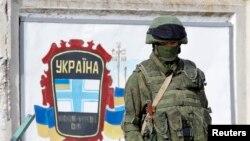 一名据信是俄罗斯军人在克里米亚一所军事基地附近站岗