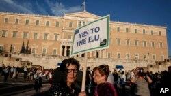 ຜຸ້ສະໜັບສະໜູນສະຫະພາບຢູໂຣບ ຖືປ້າຍປະທ້ວງ ລະຫວ່າງການເດີນຂະບວນ ຢູ່ຕໍ່ໜ້າສະພາ ທີ່ນະຄອນ Athens.