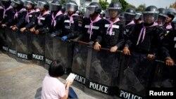 Một người biểu tình chống chính phủ ngồi cầu nguyện phía trước lực lượng cảnh sát Thái Lan gần Tòa nhà Chính phủ ở Bangkok, ngày 14/2/2014.