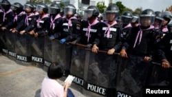 An anti-government protester sits on the ground praying in front of a line of Thai police near Government House in Bangkok, Feb. 14, 2014.