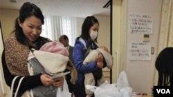 Ibu-ibu dengan anak balita mendapat air minum dalam kemasan di sebuah klinik di Tokyo, Kamis (24/3).