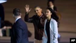 Presiden Barack Obama melambaikan tangannya didampingi putrinya, Malia, saat hendak memasuki pesawat Air Force One di bandara Internasional Buenos Aires, Argentina (25/3).