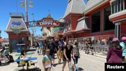 FILE - People, mostly maskless, walk past the Giant Dipper rollercoaster ride at the Santa Cruz Beach Boardwalk, in Santa Cruz, California, June 28, 2021.