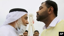 Hassan Mushaima, a Bahraini rights activist and a prominent Shi'ite opposition leader, wears a mask against tear gas as he is greeted by an anti-government demonstrator at Pearl roundabout in Manama, Bahrain, March 13, 2011