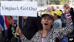 A Thai anti-government protester holds a placard and chants slogans during a rally at Victory Monument intersection, Jan. 21, 2014 in Bangkok, Thailand.