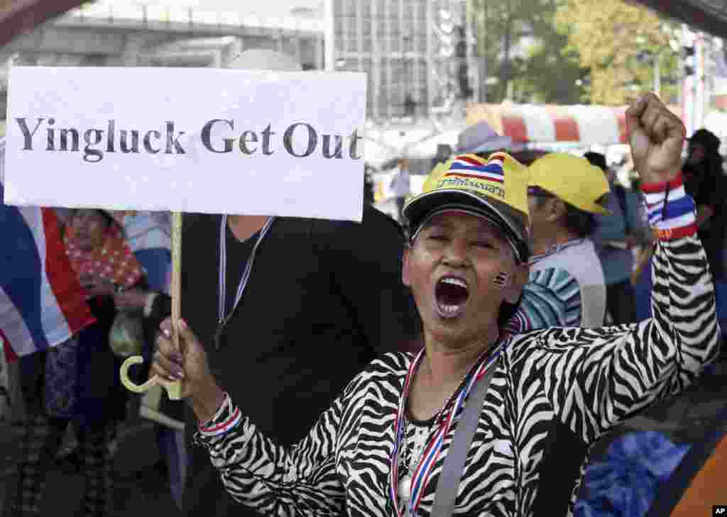 An anti-government protester holds a placard and chants slogans during a rally at Victory Monument intersection in Bangkok, Jan. 21, 2014.