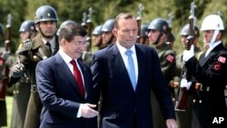 Turkish Prime Minister Ahmet Davutoglu, left, and his Australian counterpart Tony Abbott inspect a military honor guard during a welcome ceremony in Ankara, April 22, 2015.