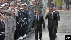 U.S. President Barack Obama (R) salutes as he walks with France's President Nicolas Sarkozy during a Franco-American alliance ceremony at the end of the G20 Summit for Heads of State and Government in Cannes, France, November 4, 2011.